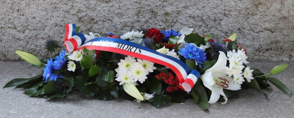Gerbe de fleur déposée au pied du monument aux morts